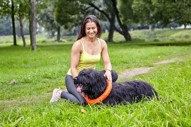 웃는 여성 소유자는 공공 공원에서 briard와 놀고 있습니다. 야외에서 큰 검은 개를 가진 젊은 여자.
