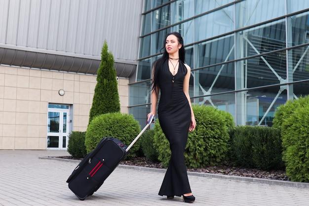 Smiling female passenger proceeding pulling suitcase through airport
