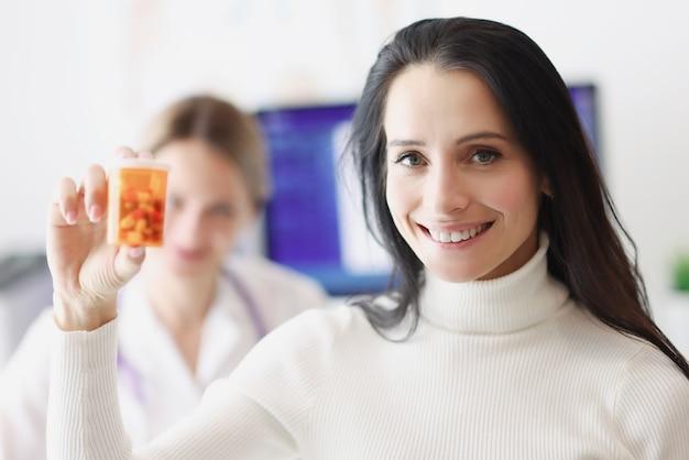 Улыбающаяся пациентка, держащая таблетки на фоне врача