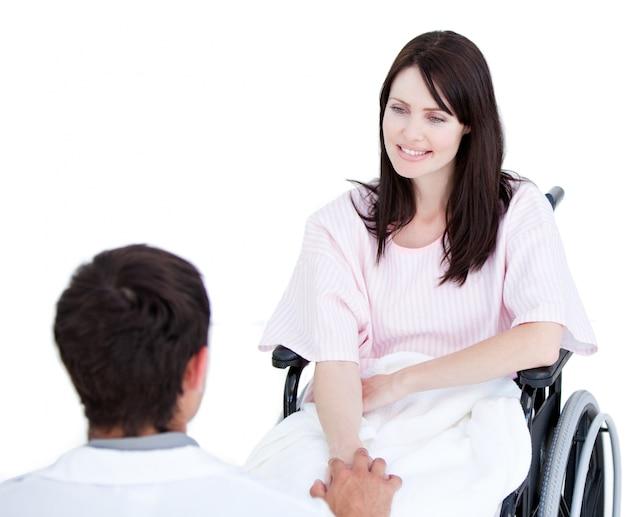 그녀의 의사와 상호 작용하는 휠체어에 웃는 여성 환자