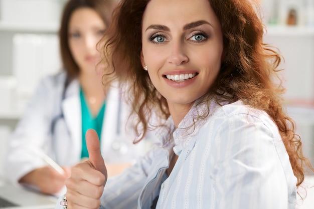 医師のオフィスで親指を立ててokサインを示す笑顔の女性患者。高レベルで質の高い医療サービスのコンセプト。最高の治療と患者ケアの概念