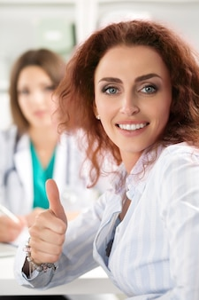 Улыбаясь пациентка показывает знак ок с большим пальцем руки вверх в офисе врача. концепция медицинского обслуживания высокого уровня и качества. лучшая концепция лечения и ухода за пациентами