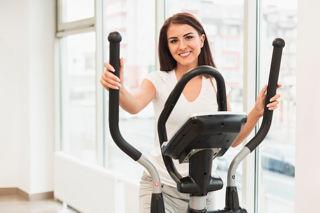 Smiling female patient working out on stepper