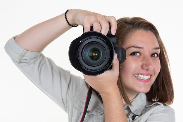 Smiling female photographer shooting you isolated on white