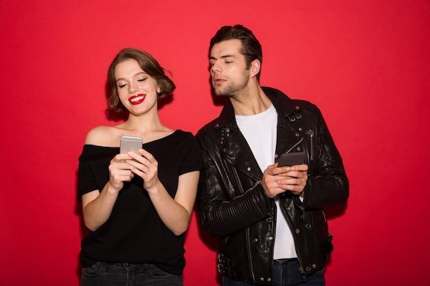 Улыбающаяся женщина-панк с помощью смартфона, а мужчина заглядывает в него