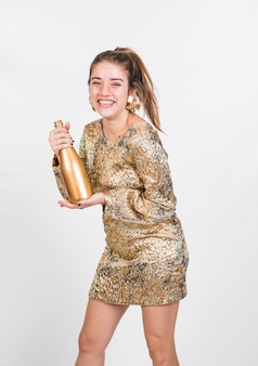 Smiling female shaking bottle of champagne
