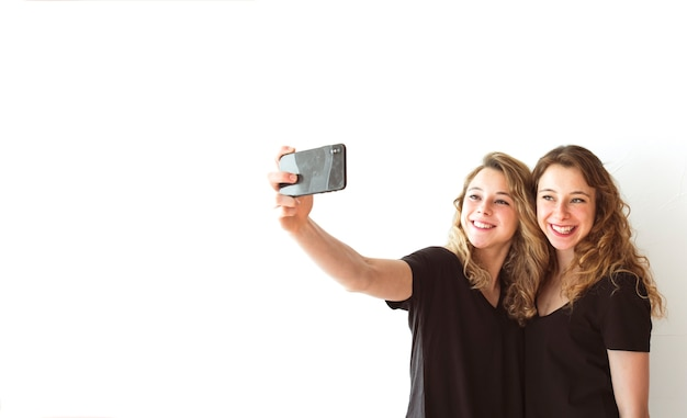 Smiling female sister taking selfie on cellphone against white backdrop