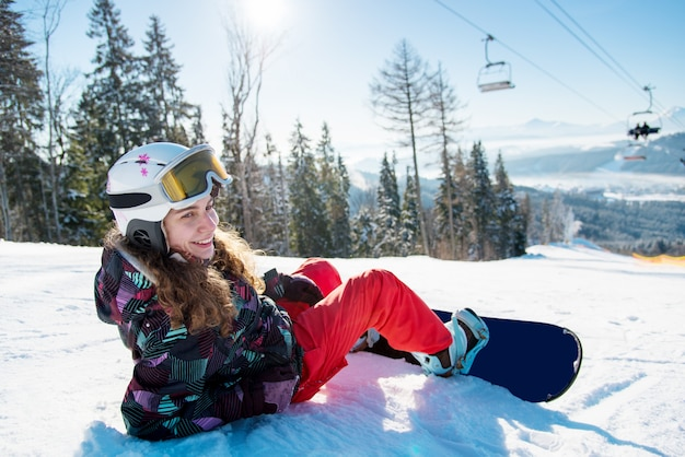 山のスキーリゾートで美しい晴れた冬の日の太陽光線のスキー場のリフトの下で雪の上に横たわる女性スノーボーダーの笑みを浮かべてください。