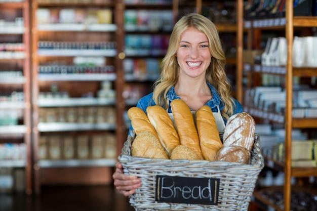 Улыбающаяся женщина-персонал держит корзину с хлебом