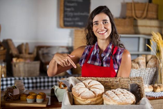 Улыбающийся женский персонал держит плетеную корзину с хлебом у прилавка