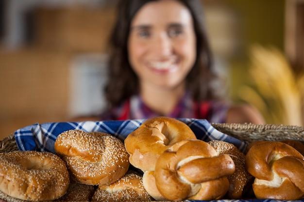 Улыбающийся женский персонал держит плетеную корзину с различным хлебом у прилавка