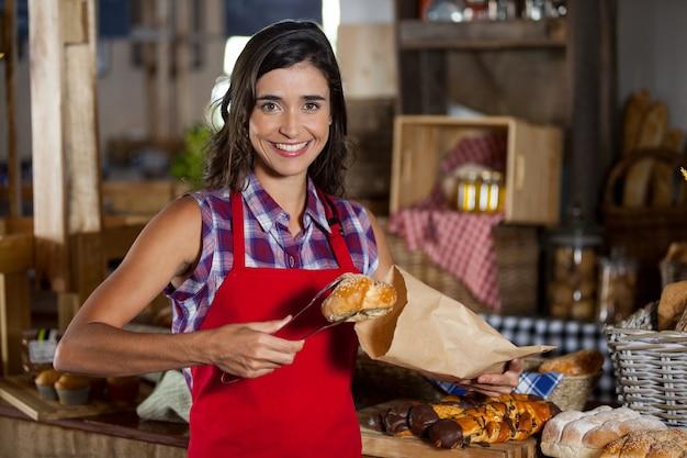 Улыбающийся женский персонал упаковывает сладкую еду в бумажный пакет на прилавке в пекарне