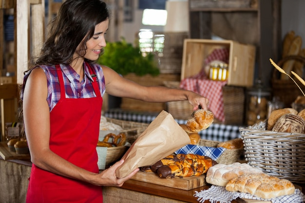 Smiling female staff packing sweet food in paper bag at counter