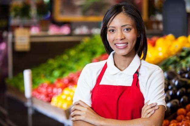 有機セクションで腕を組んで立っている笑顔の女性スタッフ
