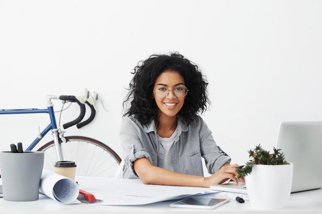 Улыбающаяся студентка-дизайнер сидит на своем рабочем месте в окружении гаджетов