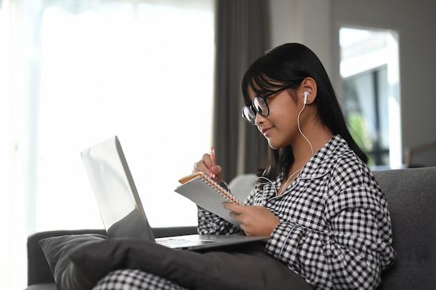 自宅のソファに座ってラップトップコンピューターでオンラインコース中に女子学生を笑顔。