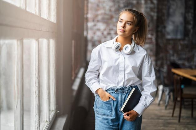 흰 셔츠와 무선 헤드폰에 웃는 여자 학생은 창 앞에 서있다.