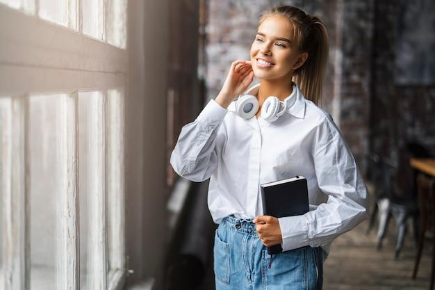 Улыбающаяся студентка в белой рубашке и беспроводных наушниках стоит перед окном.