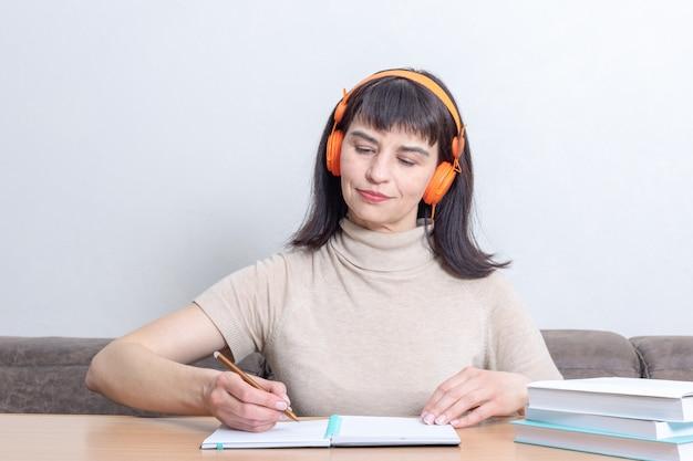 Улыбающаяся студентка слушает удаленный аудиокурс в наушниках и пишет что-то в блокноте, сидя за столом