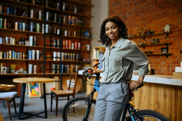 Smiling female student poses with bicycle in cafe