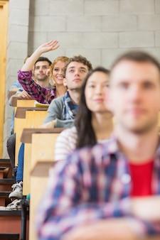 Smiling female student raising hand in classroom