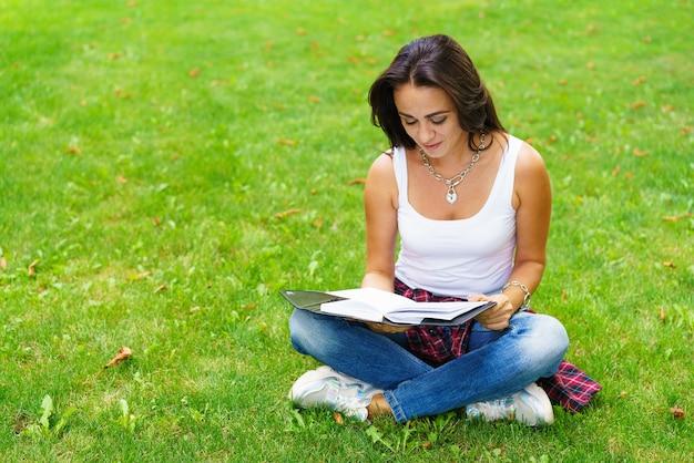 메모장을 손에 들고 잔디에 앉아 시험을 준비하는 웃는 여학생. 교육 및 원격 작업 개념입니다. 부드러운 선택적 초점입니다. 잠겨있는 표정으로 백인 소녀