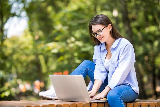Улыбающаяся студентка, сидящая на скамейке с ноутбуком на открытом воздухе
