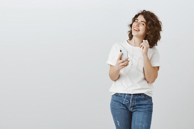 Улыбающаяся студентка снимает наушники и смотрит на вопрос, слушает музыку