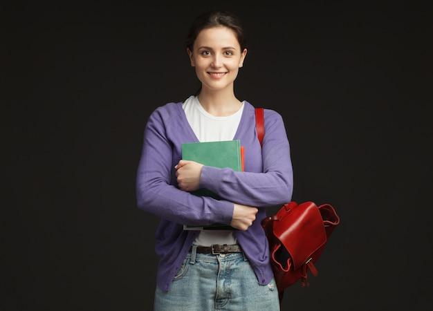 本とバックパックを分離して笑顔の女子学生