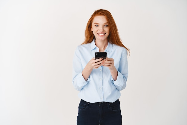Smiling female student with ginger hair and blue eyes using mobile phone, looking happy at at front, standing over white wall