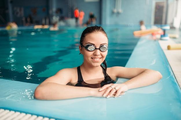 ゴーグルで笑顔の女性スイマーはプールで泳ぎます。トレーニング、水泳スポーツの水着の女性
