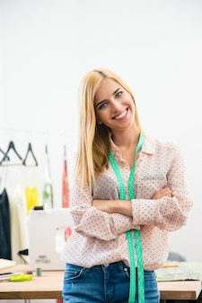 Smiling female tailor with hands crossed
