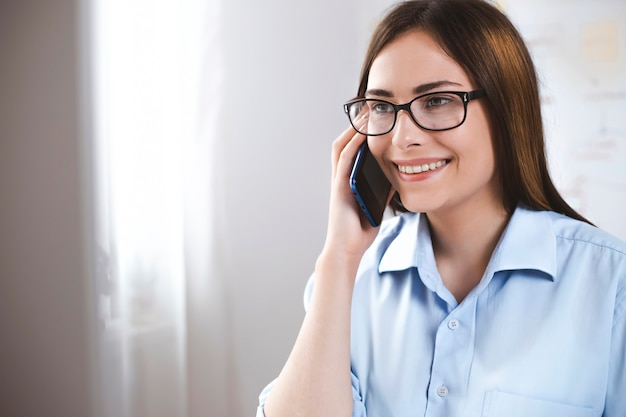 Smiling female talking on the phone. happy business woman