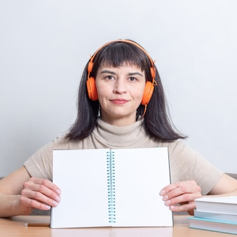 Smiling female teacher with headphones holding a blank exercise book