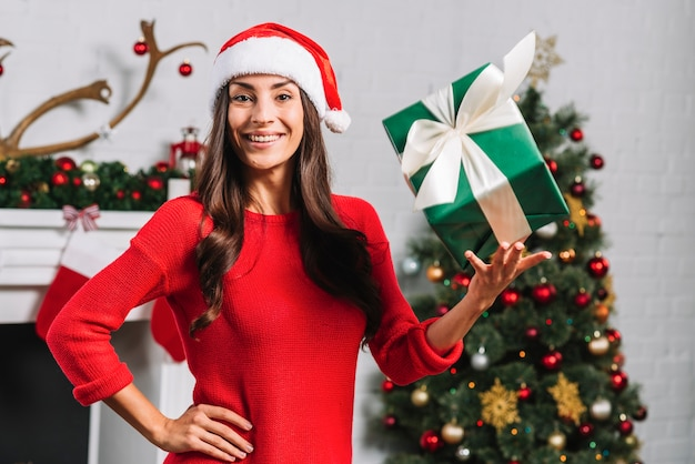 Smiling female tossing up gift box