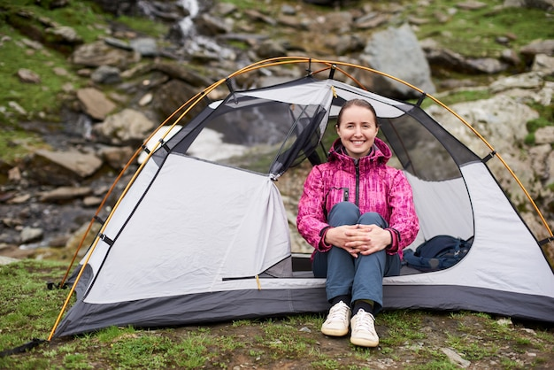 Smiling female tourist sitting at tent entrance near beautiful rocky slope in mountains