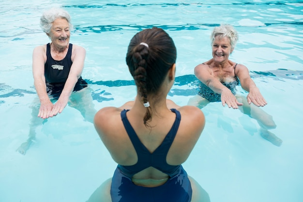 Smiling female trainer with senior women exercising in swimming pool