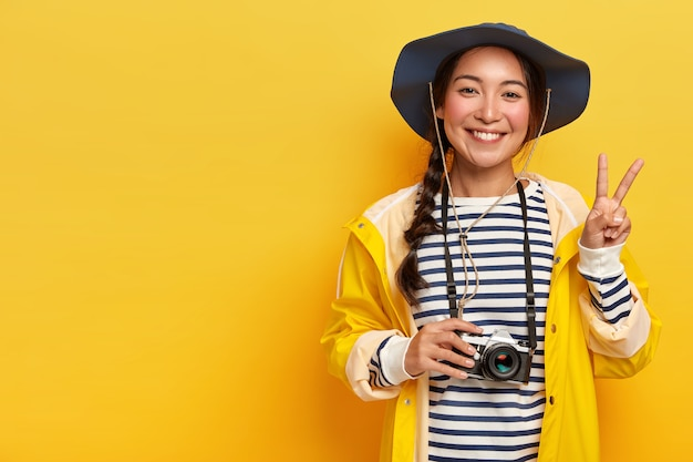 Smiling female traveler makes peace gesture, takes photos with retro camera, wears hat, striped sweater and raincoat, enjoys exciting travel, poses against yellow background, copy space for text