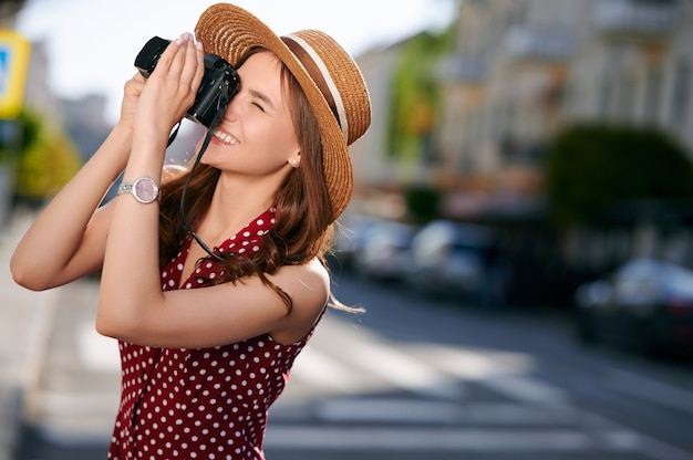 Smiling female traveler takes pictures on camera city buildings outdoors summer