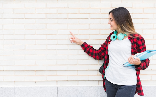 Smiling female university student holding books in hand pointing the finger on white painted wall