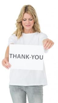 「ありがとう」紙を持っている女性のボランティアを笑って