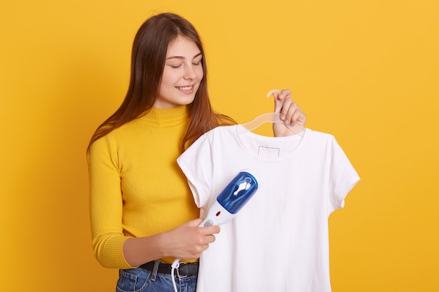 Smiling female wearing yellow casual sweater holding white t shirt on hangers and steaming iron, looking at her attire, preparing for dating, stands against yellow wall.