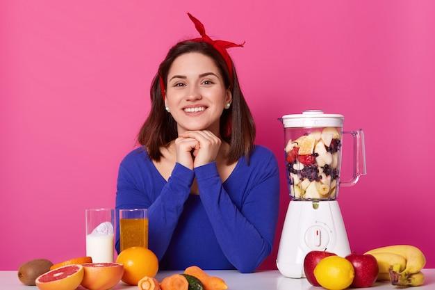 웃는 여성, 빨간 머리띠를 착용하고, 파란색 점퍼를 착용하고, 팔로 그녀의 머리를 잡고, 신선한 재료를 준비하기 위해 다른 재료, 과일 및 야채를 사용하고, 건강한 라이프 스타일을 이끌어냅니다. 다이어트 개념.