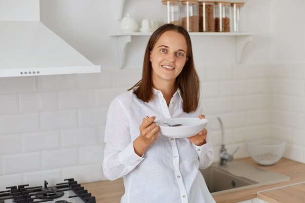 Smiling female with dark hair wearing white shirt standing with plate in hand, looking at camera, having soup for breakfast, posing in light kitchen in morning.
