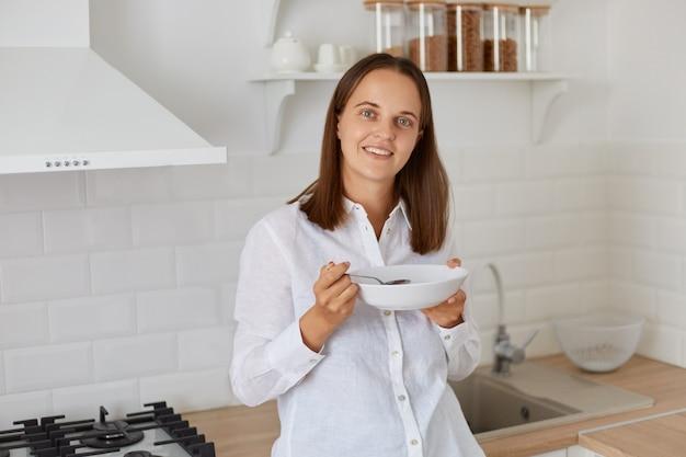 プレートを手に立って、カメラを見て、朝食にスープを飲んで、朝の明るいキッチンでポーズをとって、白いシャツを着て黒髪の女性を笑顔。