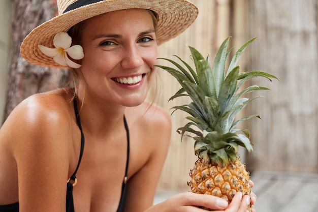 Smiling female with perfect slim body, tanned skin, wears straw hat, holds pineapple