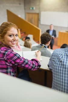 강당에서 학생과 교사와 웃는 여자