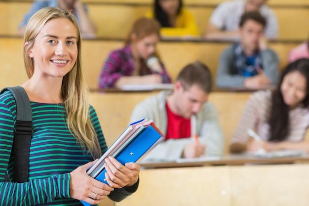 강당에 앉아있는 학생들과 웃는 여자