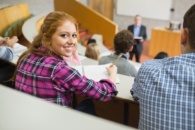 Smiling female with students and teacher in lecture hall