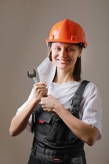 조정에 대 한 렌치를 들고 웃는 여성 노동자